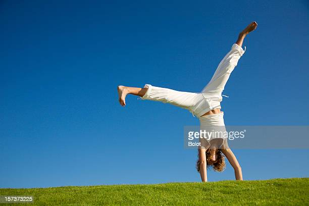 young woman doing cartwheel on grass - cartwheel stock pictures, royalty-free photos & images