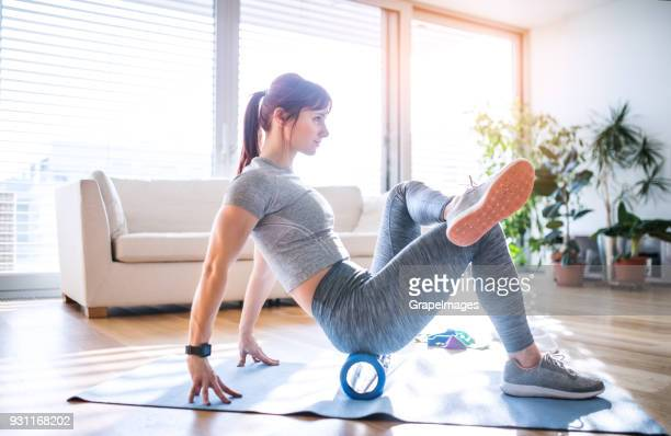 young woman doing exercise at home. - de rola imagens e fotografias de stock