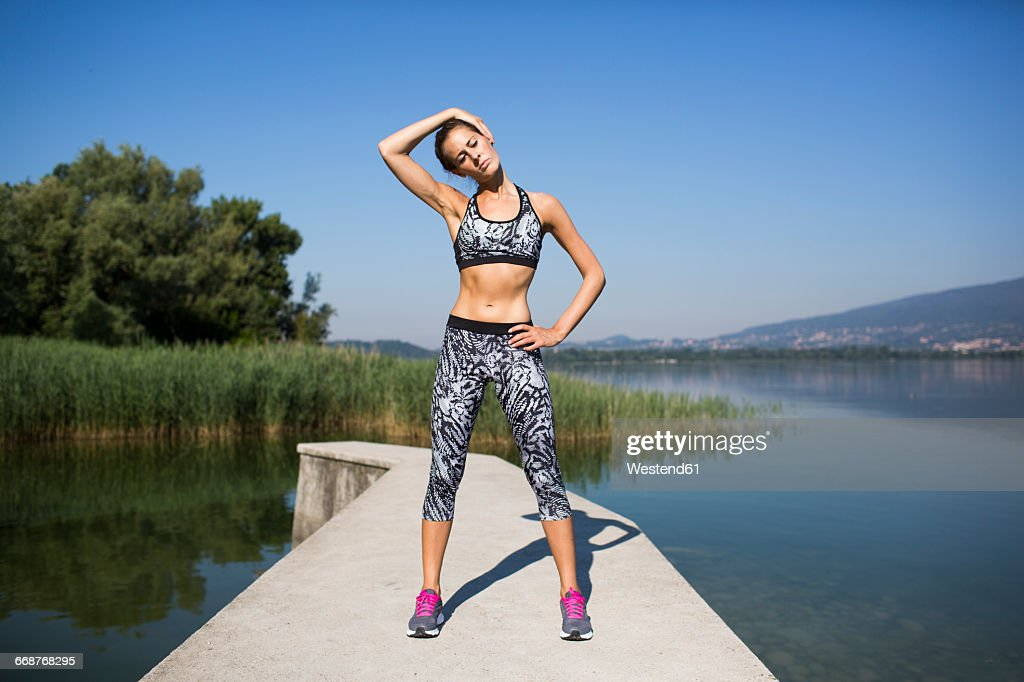Young woman doing exercise at lake : Stock Photo