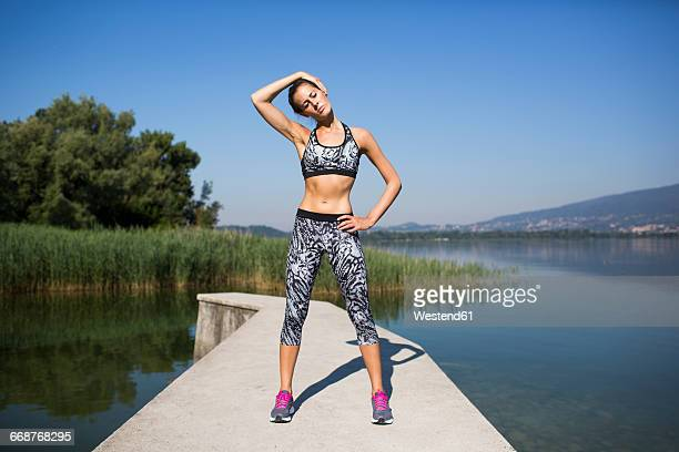 young woman doing exercise at lake - female reproductive system stock photos and pictures