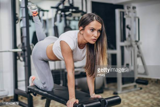 young woman doing exercise for buttocks - culi foto e immagini stock