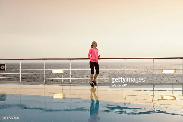 Young woman doing exercises on a shipdeck, cruise ship, Mediteranean Sea