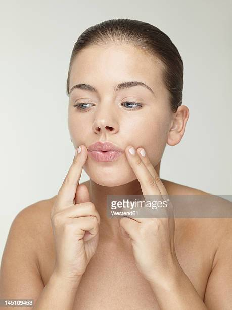 Young woman doing face massage, close up