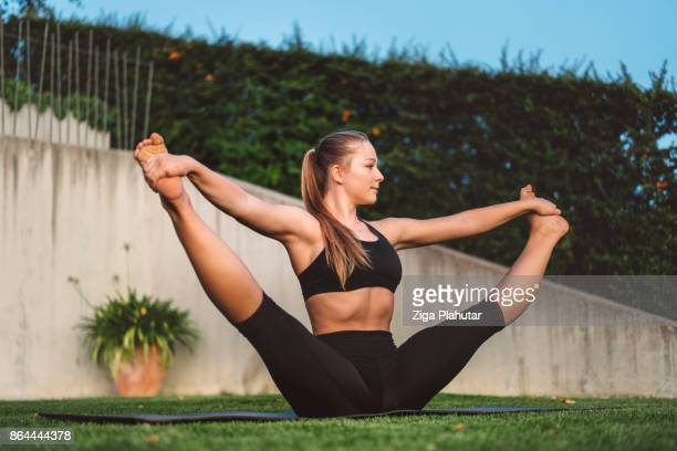 young woman doing flexibility training outdoors - chubby legs stock photos and pictures