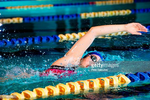 Young woman doing front crawl in swimming pool