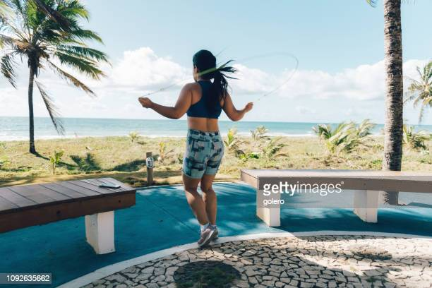 young woman doing gym with skipping rope at beach