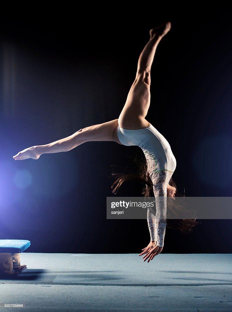 Young woman doing gymnastics jump : Stock Photo