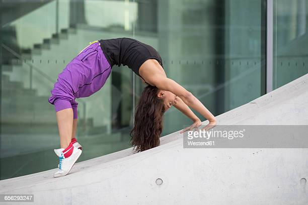 Young woman doing gymnastics outdoors