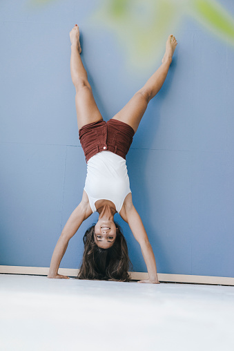 Young woman doing handstand against wall - gettyimageskorea