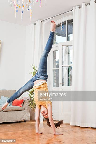 Young woman doing handstand in her living room