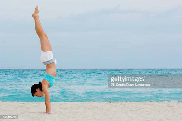 Young woman doing handstand on beach.