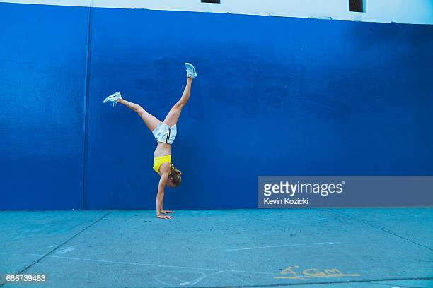 Young woman doing handstand outdoors in front of blue wall