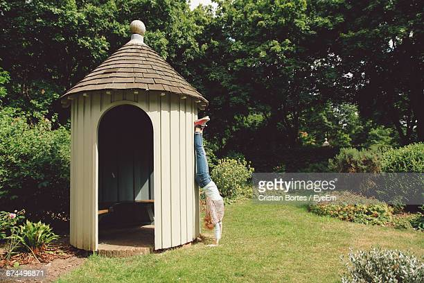 Young Woman Doing Handstand While Leaning On Gazebo In Park