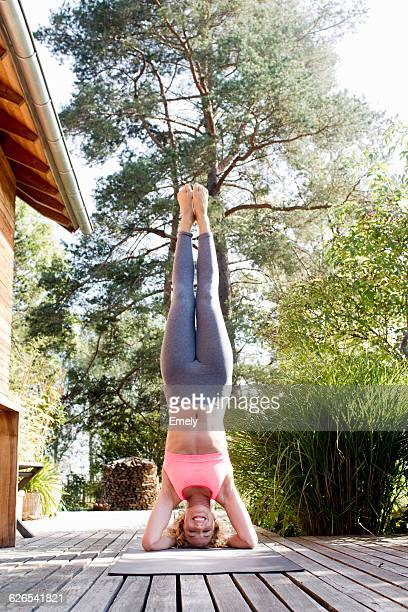 Young woman doing headstand in garden