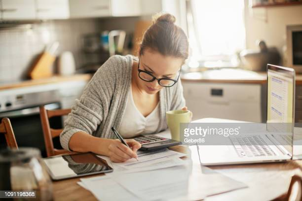 young woman doing her bills - financial bill stock pictures, royalty-free photos & images