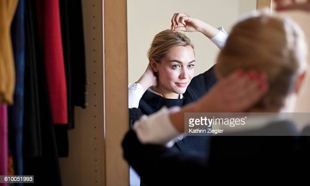 young woman doing her hair in front of mirror