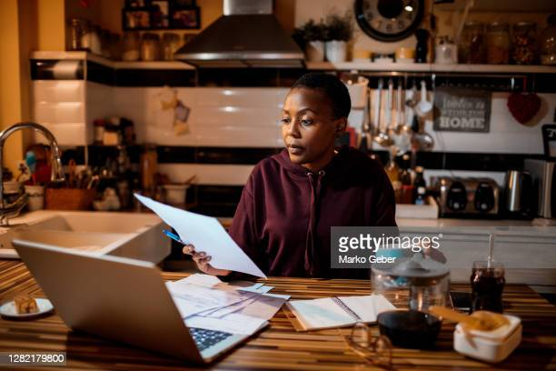 young woman doing home finances in the evening - budget stock pictures, royalty-free photos & images