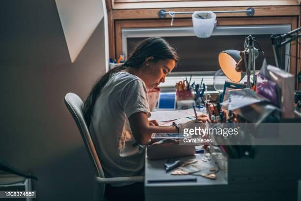 young  woman doing homework at home - schulbuch stock-fotos und bilder