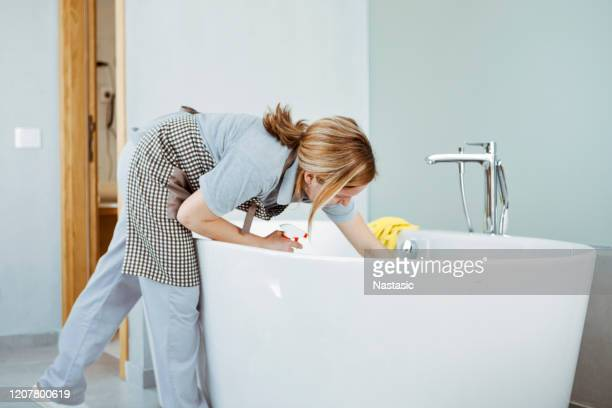 young woman doing household chores ,cleaning bathroom tub - housework stock pictures, royalty-free photos & images