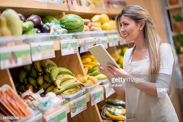 Young woman doing inventory at a food market