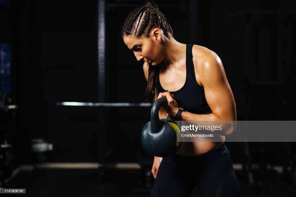 Young woman doing kettlebell exercise at gym : Stock Photo