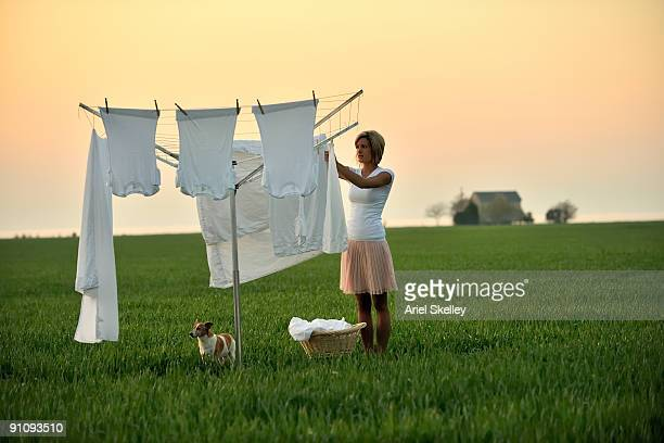 Young Woman Doing Laundry in Field at Sunrise