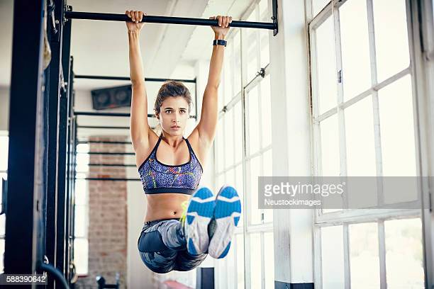 Young woman doing leg raises on pull-up bar in gym