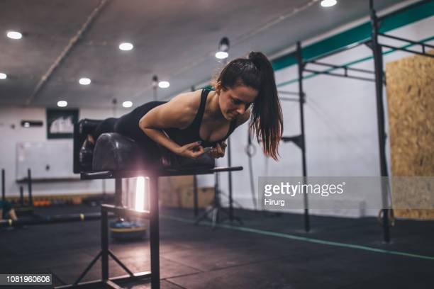 young woman doing low back exercise - lower back stock pictures, royalty-free photos & images