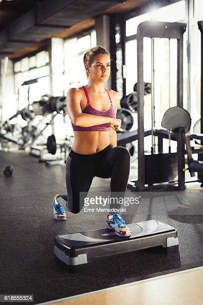 Young woman doing lunges on step aerobics equipment at gym.