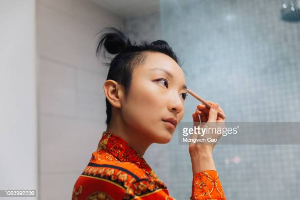 young woman doing makeup - showus stock pictures, royalty-free photos & images