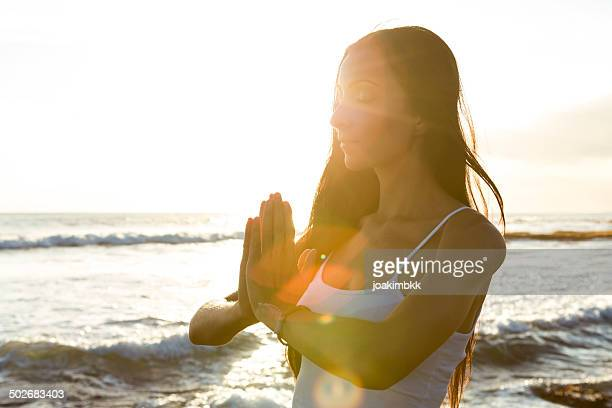 Young woman doing meditation at sunset