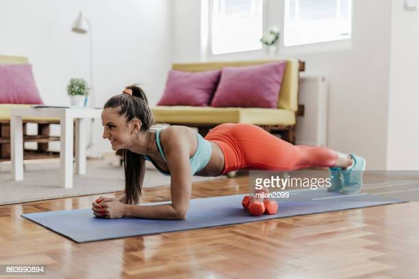 young woman doing plank exercise in her home - home workout stock pictures, royalty-free photos & images