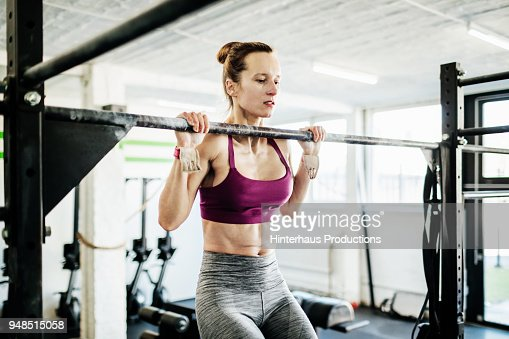 Young Woman Doing Pull Ups At Gym