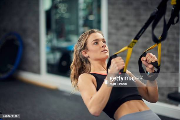 Young woman doing pull ups on exercise handles in gym