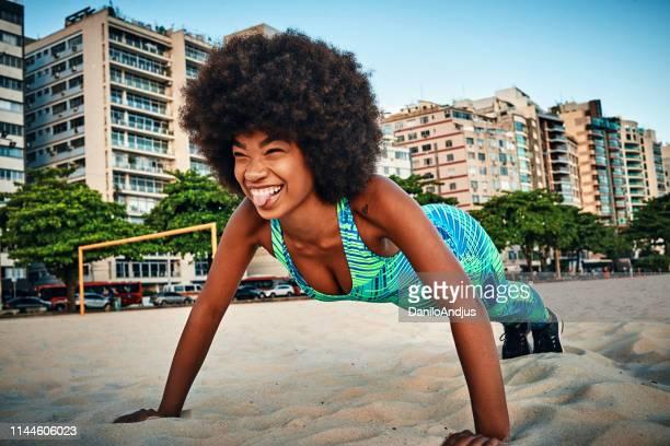 jonge vrouw doet push ups op het strand - hardnekkigheid stockfoto's en -beelden