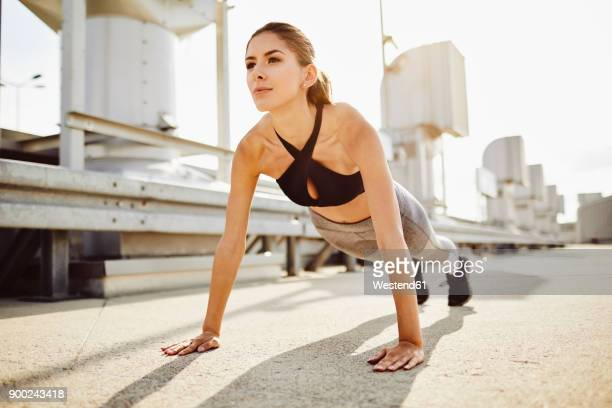 young woman doing pushups in the city - push ups stock pictures, royalty-free photos & images