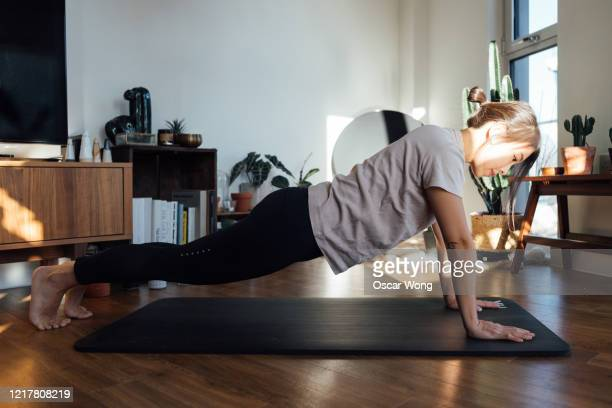 young woman doing push-ups on exercise mat at home - push ups stock pictures, royalty-free photos & images