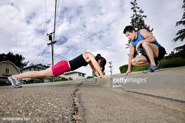 Young woman doing push-ups on street, instructor watching