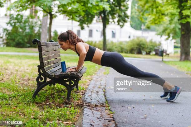 公園のベンチで腕立て伏せをしている若い女性 - 自重トレーニング ストックフォトと画像