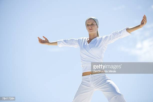 Young woman doing relaxation exercises, low angle view