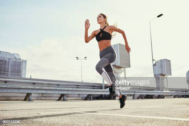 young woman doing running exercises in the city - jogging stock pictures, royalty-free photos & images