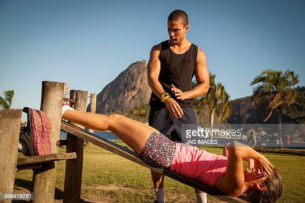 Young woman doing sit ups on wooden workbench in park