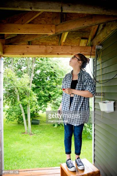 young woman doing some diy around the house outdoors. - one young woman only stock pictures, royalty-free photos & images