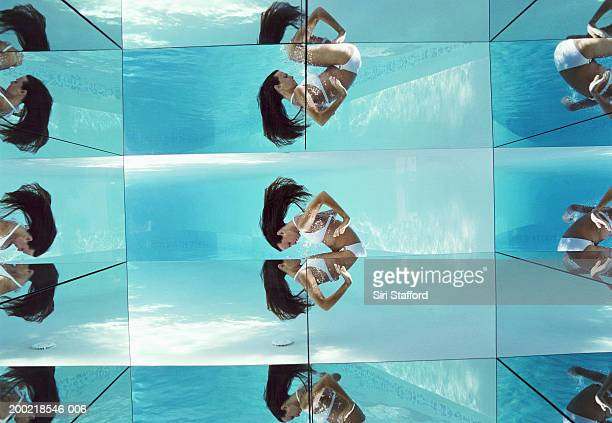 Young woman doing somersault underwater, reflection on glass