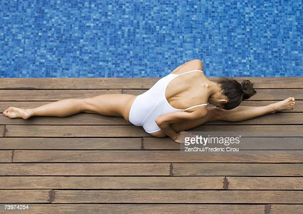 Young woman doing splits by edge of pool, high angle view