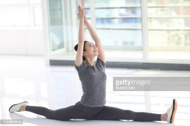 young woman doing splits in floor - 体操競技 ストックフォトと画像