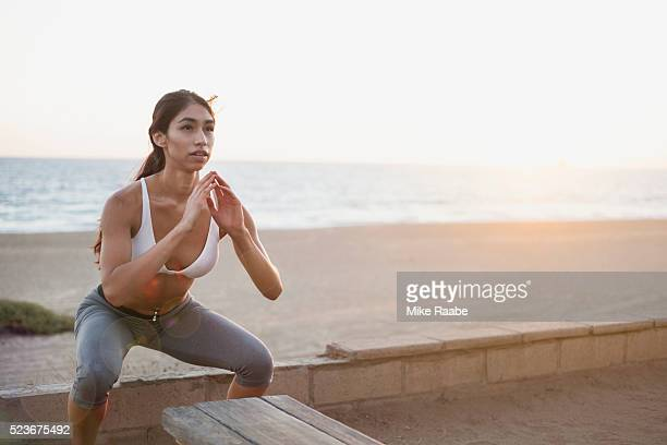 young woman doing squat jumps on beach - crouching stock pictures, royalty-free photos & images