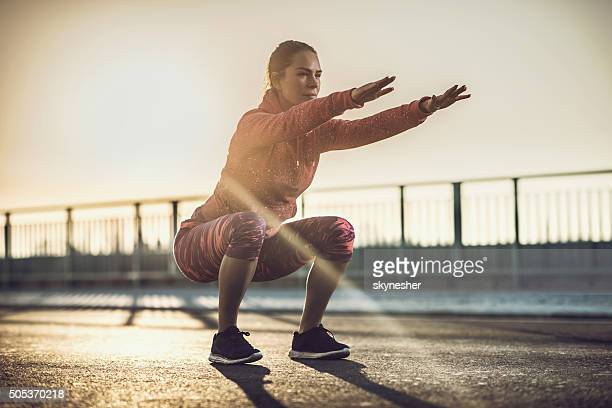 young woman doing squats on a road at sunset. - hurken stockfoto's en -beelden