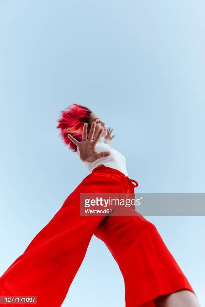 young woman doing stop gesture while standing against blue sky - red pants stock pictures, royalty-free photos & images