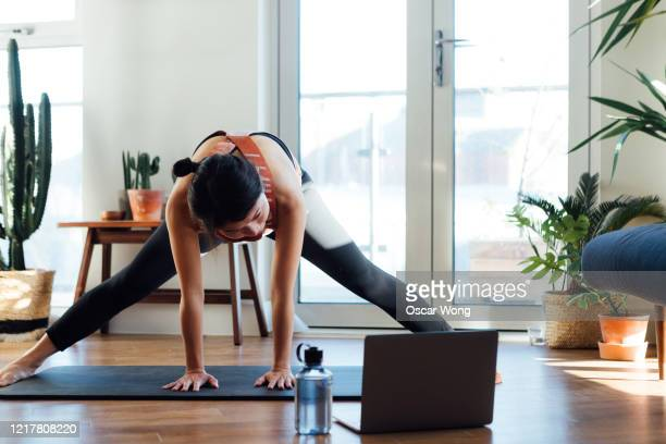 young woman doing stretching exercise in front of laptop at home - yoga stock pictures, royalty-free photos & images